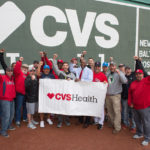 VETERANS FROM ACROSS New England pose on the field at Fenway Park at the CVS Health Baseball Skills Camp for Veterans – a special event for veterans hosted by CVS Health in partnership with the Boston Red Sox. /COURTESY CONSTANCE BROWN PHOTOGRAPHY