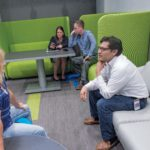 COLLABORATION: Amgen Rhode Island employees decided to transform some extra space into a coffee shop and game room where staff can meet and relax. From left, Patty Sprague, facilities and engineering; Tara Urban, senior manager corporate affairs; Ryan Meyers, supply chain; Bruno Tapia, facilities director. / PBN PHOTO/MICHAEL SALERNO