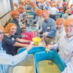 IN SERVICE: Amica's management team packs meals to support the nonprofit Feeding Children Everywhere during a corporate retreat held in Denver. / COURTESY AMICA