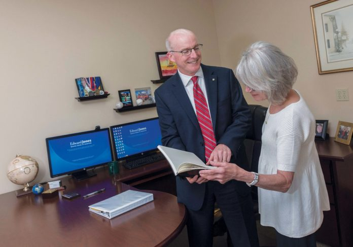 FAMILY FEEL: Edward Jones financial adviser John Leary talks with Susan Comeau, senior branch office administrator, at the company's office in Barrington. / PBN PHOTO/MICHAEL SALERNO