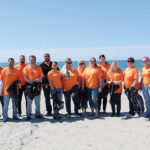 MAKING A DIFFERENCE: Embrace Home Loans supports staff volunteering efforts, such as cleaning up the Ocean State's beaches. / COURTESY EMBRACE HOME LOANS