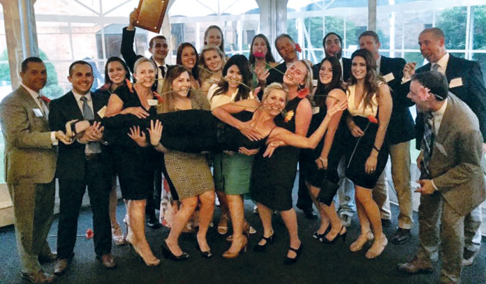 REPEAT PERFORMANCE: Celebrating their 2016 selection as one of the Best Places To Work is the Performance Physical Therapy staff, including CEO Michelle Collie, being held aloft. / COURTESY PERFORMANCE PHYSICAL THERAPY