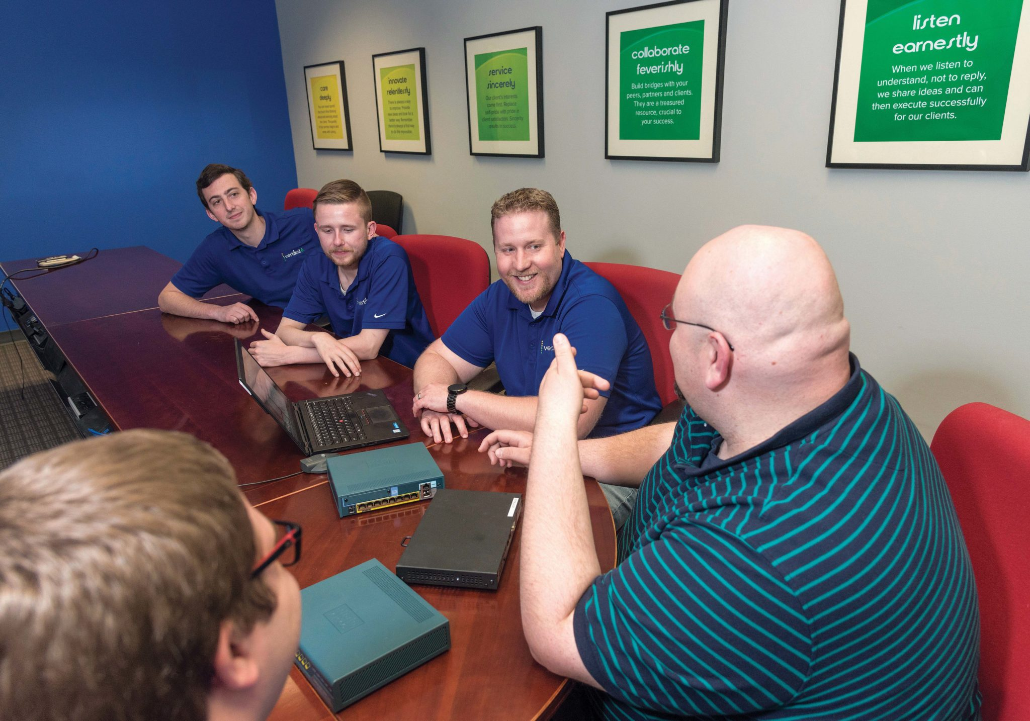 Strong staff: Vertikal6 staff in a network design meeting. From left, in background clockwise, James Green, systems engineer; Jonathan Essex, engineering manager; Drew Hill, field service engineer; Joe Lefrancois, senior network engineer; and Dean Gerjets, dedicated service engineer. / PBN PHOTO/MICHAEL SALERNO