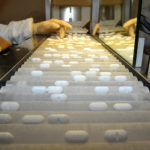 AN EMPLOYEE USES a machine that sorts pills. / BLOOMBERG FILE PHOTO/ANTOINE ANITONIOL