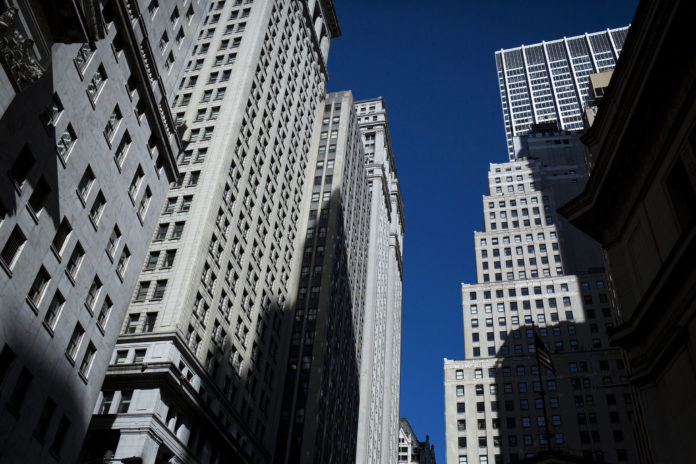 A TREASURY DEPARTMENT REVIEW is expected propose measures to dial back the Dodd-Frank Act, rather than repeal it. Above, buildings stand on Wall Street near the New York Stock Exchange. / BLOOMBERG FILE PHOTO/JOHN TAGGART