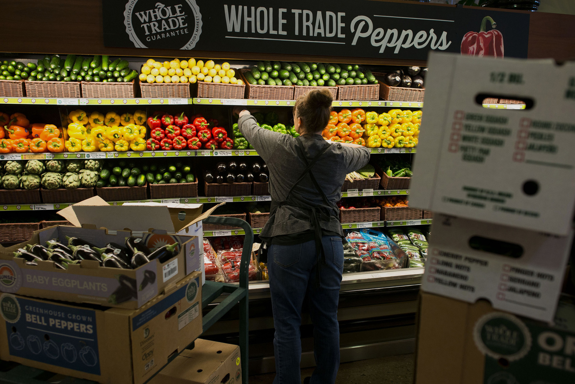 AN EMPLOYEE STOCKS the shelves with fresh peppers in the produce section of a Whole Foods Market Inc. store in Dublin, Ohio, U.S., on Friday, Nov. 7, 2014. Whole Foods Market Inc. posted fiscal fourth-quarter profit that topped analysts' estimates as the grocery-store chain slashed prices to win over bargain-hunting shoppers. The shares soared the most in four years. BLOOMBERG FILE PHOTO/ TY WRIGHT
