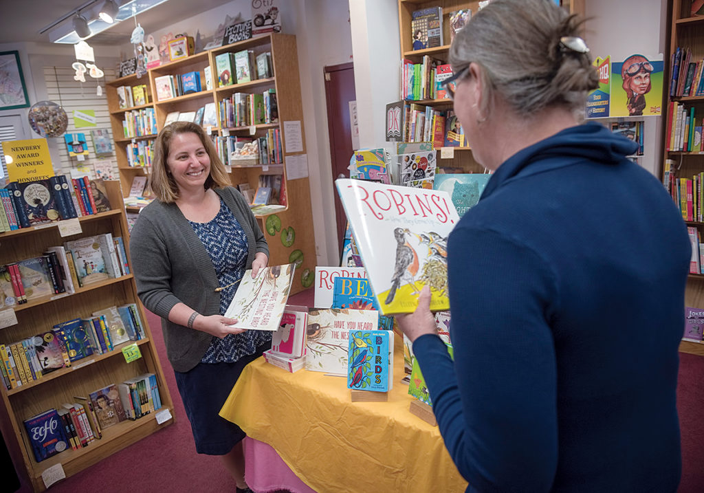 INDEPENDENT OWNER: Jennifer Kandarian, left, store manager at Books on the Square in Providence, speaks with Robin Gross, children's book buyer. Top left, Kandarian arranges books for display. / PBN PHOTO/MICHAEL SALERNO