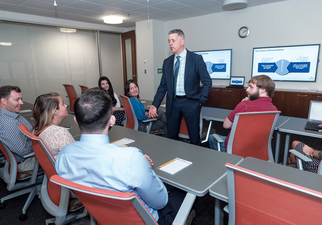 PROACTIVE APPROACH: Tim Hebert, chief client officer for Carousel Industries of North America Inc., in Exeter, gives an in-house job-training program that's produced dozens of employees for his company, Atrion, which was acquired by Carousel Industries last year. / PBN PHOTO/MICHAEL SALERNO