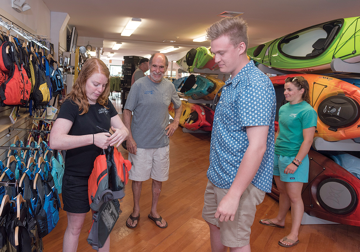 NEW LOCATION: Jeff Shapiro, owner of The Kayak Centre of Rhode Island, recently relocated to 70 Brown St., in North Kingstown. From left, Mollie Goodwin, manager; Jeff Shapiro, owner; Sam Loomis of East Greenwich; and Abbey Torres of Cranston. Loomis was trying on flotation vests. / PBN PHOTO/MICHAEL SALERNO