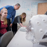 THE FUTURE IS NOW: Walt Besio, center, professor of biomedical engineering at URI and owner of CREmedical, works with company intern Jessika Decker, left, and Rachel Bartels, product manager for CREmedical, while testing the National Science Foundation-supported biomedical electrode he patented that measures brain activity and can be used to potentially stop life-threatening seizures.  / PBN PHOTO/­MICHAEL SALERNO