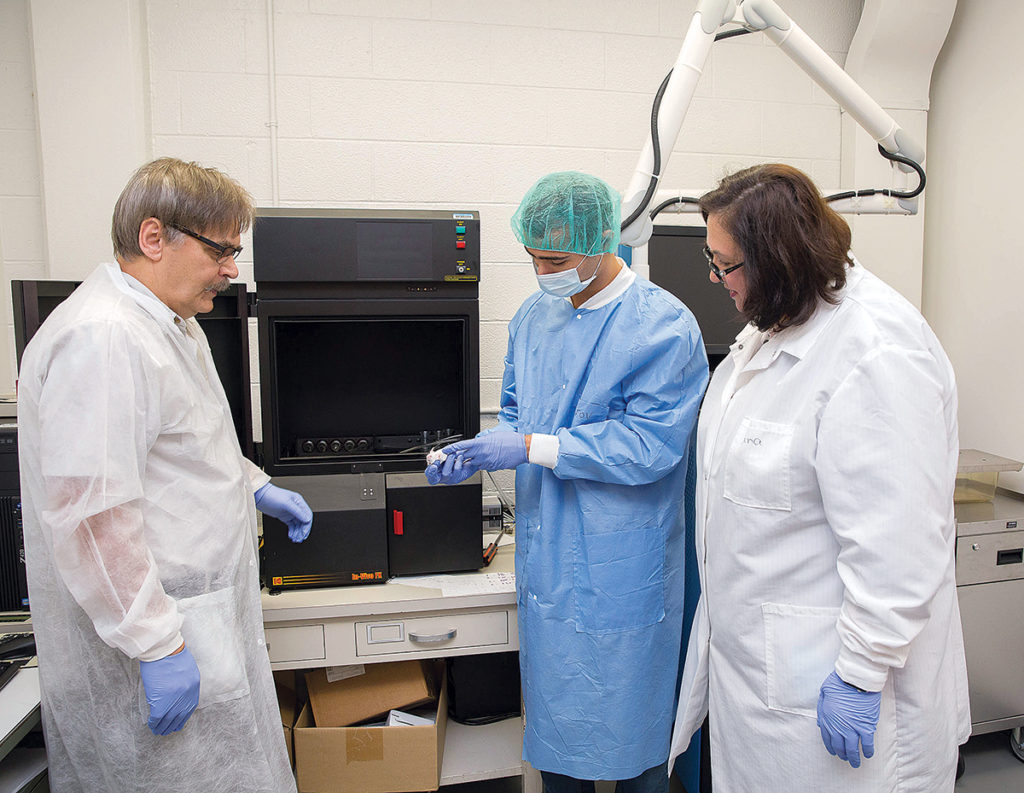LAB WORK: University of Rhode Island biophysicists Oleg Andreev, left, and Yana Reshetnyak, right, who have successfully obtained patents, work in their lab with URI student Troy Crawford. The biophysicists are focused on improving detection of cancer cells and targeting radiation therapy toward cancer cells. / PBN PHOTO/TRACY JENKINS