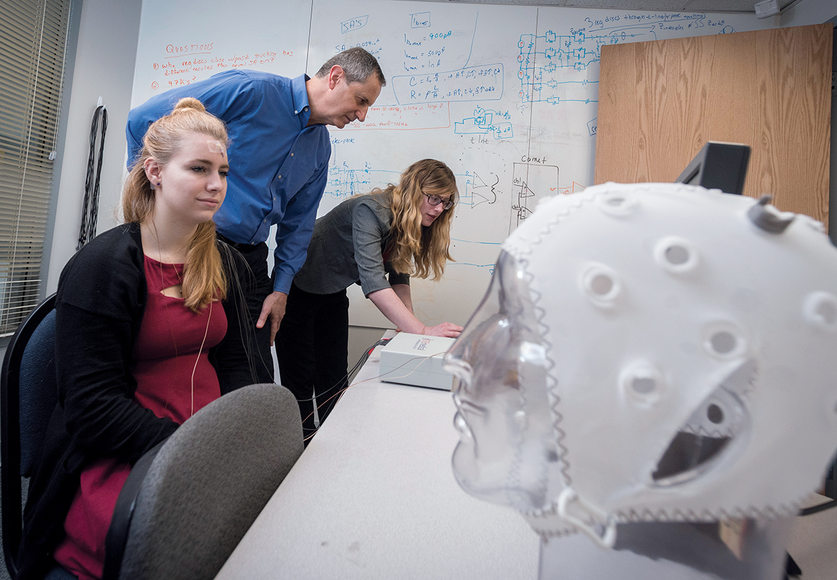 URI STAR: Walt Besio, professor of biomedical engineering at the University of Rhode Island and owner of CREmedical, secured $6 million in a National Science Foundation grant in 2015, a year after he earned two patents for a biomedical electrode that measures brain activity and can be used to potentially stop life-threatening seizures. From left, Jessika Decker, test subject and intern at CREmedical, Besio and Rachel Bartels, product manager at CREmedical. / PBN PHOTO/MICHAEL SALERNO