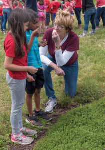 FRESH HERBS: Community School first-graders Emma Rasomgath, 6, left, and Daniel Dubon, 7, smell fresh-cut mint leaves during a visit to the Historic Metcalf-Franklin Farm in Cumberland while Pamela Thurlow, Historic Metcalf-Franklin Farm Preservation Association president, gives a talk about herbs grown on the farm. / PBN PHOTO/MICHAEL SALERNO