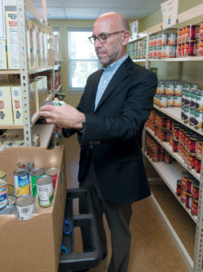 SEEKING SUPPORT: Rhode Island Community Food Bank CEO Andrew Schiff stocks shelves at the Olneyville Food Center in Providence. Schiff says if the food bank's state allocation of $175,000 were doubled, it would help with summer purchases, as food donations are more prevalent in the fall and winter months, coinciding with the holidays. / PBN PHOTO/MICHAEL SALERNO