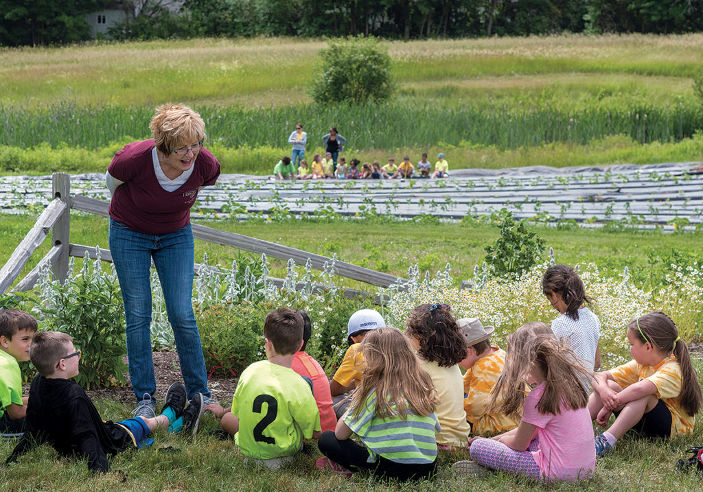 EDUCATION & DONATION: Pamela Thurlow, president of the Historic Metcalf-Franklin Farm Preservation Association in Cumberland, gives a talk to first-graders from Community School about herbs grown on the farm, which donates an average of 16,044 pounds of fresh fruits and vegetables each year to the Rhode Island Community Food Bank. / PBN PHOTO/MICHAEL SALERNO