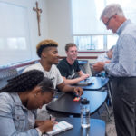 CONTINUING EDUCATION: Joe Gemma, right, assistant dean at Providence College, talks with students, from left, Dacaria Desseau, Nate Watson, Andrew Fonts and Ben Rose, during his Principles of Business Management summer school class. / PBN PHOTO/­MICHAEL SALERNO