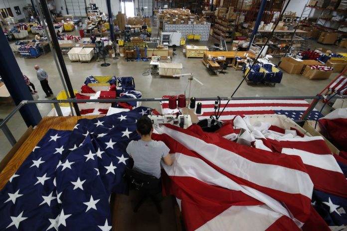A WORKER SEWS an American flag at the FlagSource facility. /BLOOMBERG FILE PHOTO/JIM YOUNG