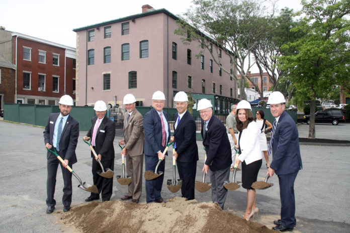 BRISTOL COUNTY SAVINGS BANK officials and New Bedford Mayor Jon Mitchell participate in the ceremonial groundbreaking of the bank's third New Bedford branch, offices of which will be located in the Candleworks building (background). Pictured, from left, are: Michael Patacao, vice president/commercial lending; Len Sullivan, first executive vice president and senior loan officer; Pete Selley, senior vice president/commercial lending; Patrick J. Murray Jr., president and CEO; Mitchell; Dennis Kelly, chairman of the board; Nancy Cabral, branch manager; and David Medeiros, vice president, regional banking officer. /COURTESY BRISTOL COUNTY SAVINGS BANK