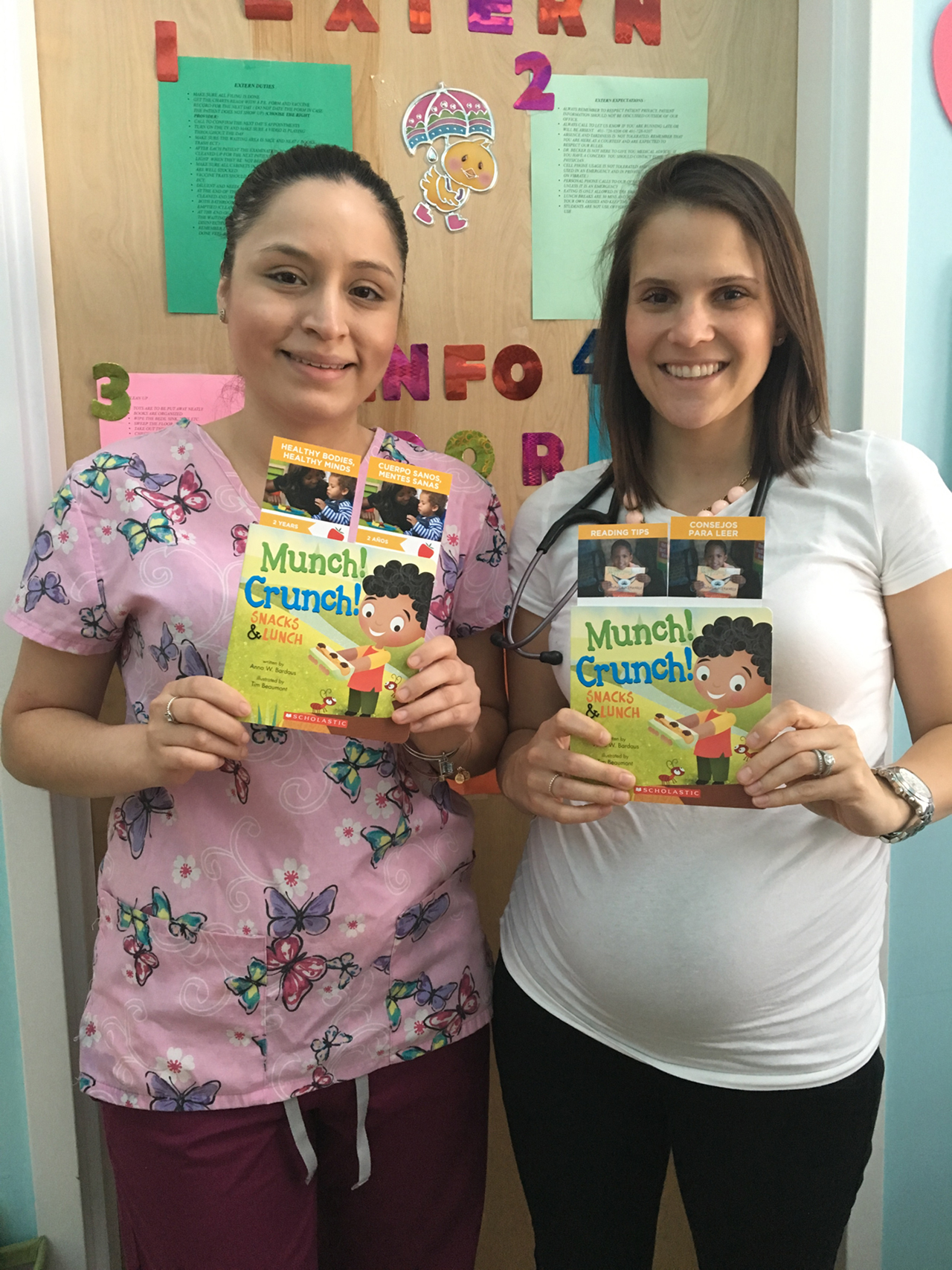 STAFF MEMBERS IN Dr. Tanya Becker's Pawtucket pediatric practice, from left, Maricarmen Ramos and Stephanie Carper, pose with the Healthy Bodies, Healthy Minds partnership's books that will be distributed to patients. /COURTESY REACH OUT AND READ RI
