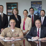 THE NAVAL UNDERSEA WARFARE Center Division Newport and the University of Rhode Island have partnered to promote undersea research and science education. Above, NUWC commanding officer Capt. Michael R. Coughlin (seated left) and URI President David M. Dooley (seated right) at the signing of the agreement on June 27. Also pictured, standing, from left to right: David Grande, NUWC acting technical director; Theresa Baus, head of NUWC's Technical Partnership Office; Kimberly Cipolla, NUWC deputy chief technology officer; George Nickolopoulos, relationship manager for the URI Business Engagement Center; and Michael Katz, URI's associate vice president of intellectual property and economic development. / COURTESY NAVAL UNDERSEA WARFARE CENTER DIVISION NEWPORT
