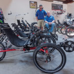 ADAPTIVE CYCLES: Scott Pellett, founder and CEO of Bike-On, was paralyzed from the waist down at age 15. Bike-On is an online retailer of recumbent trikes and adaptive cycles. With Pellett is employee Chris Coyne. / PBN PHOTO/MICHAEL SALERNO