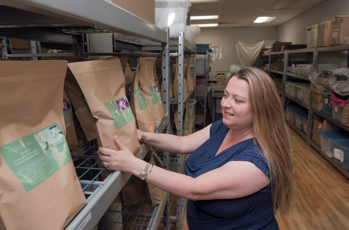 ORGANIC HEALTH: Kimberly Cornwell, owner and founder of Celadon Road Inc., an organic health and products company that sells mostly online, holds the refill size of her lavender laundry detergent, which has all-natural ingredients. / PBN PHOTO/MICHAEL SALERNO