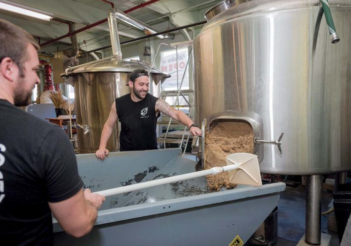 BREWING PROCESS: Co-owners Wes Staschke, left, and Josh Dunlap, take the spent grain out of the mash tun during the process of brewing a batch of ale at Whalers Brewing Co. in South Kingstown.   / PBN PHOTO/MICHAEL SALERNO