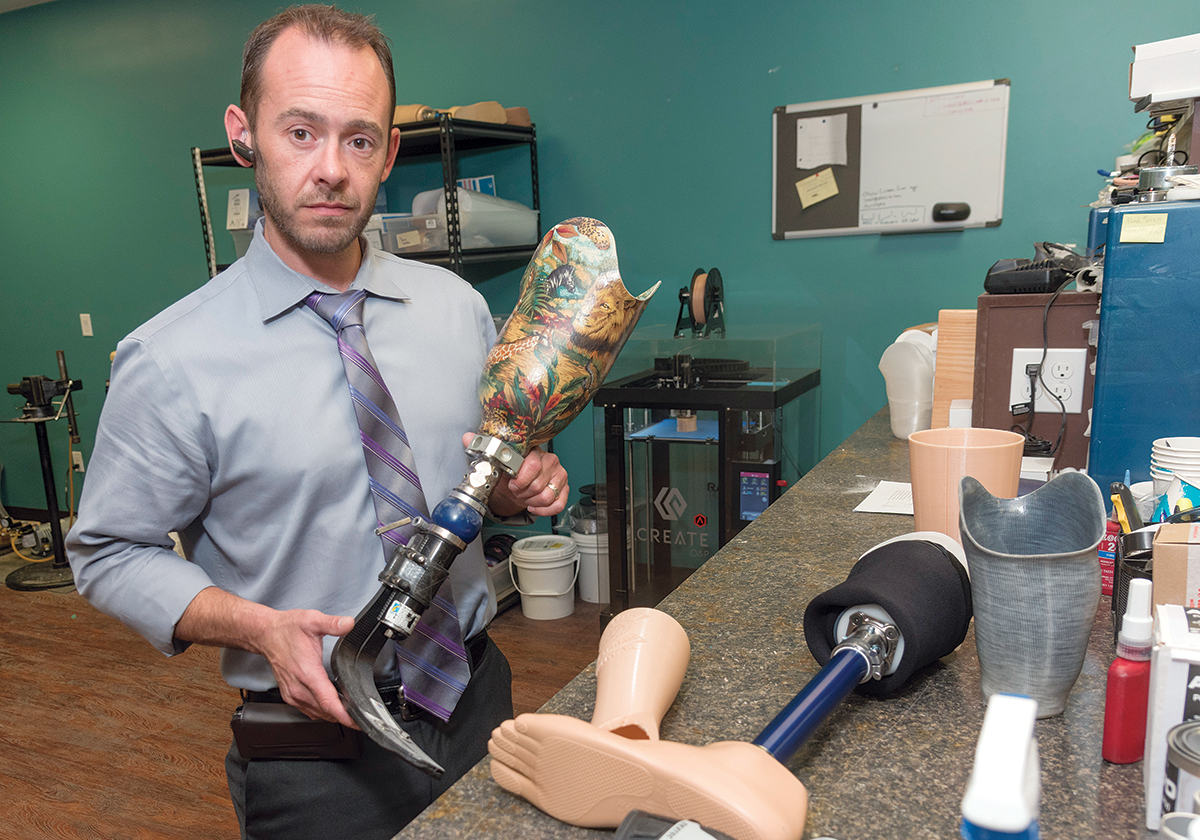 HANDS-ON: Jonathan Teoli, owner of Rhode Island Limb Co. in Cranston, works with some of the prosthetics he produces. He designs and fits each device by hand. / PBN PHOTO/MICHAEL SALERNO