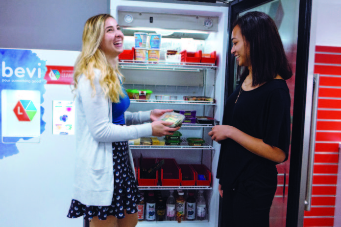 BETTER CHOICES: Gilbane has replaced unhealthy vending-machine snacks with more nutritious options. Alia Sasa, left, an instructional designer, and Thien Nguyen, HRIS administrator, sort through the options at the company's Providence headquarters. / PBN PHOTO/RUPERT WHITELEY