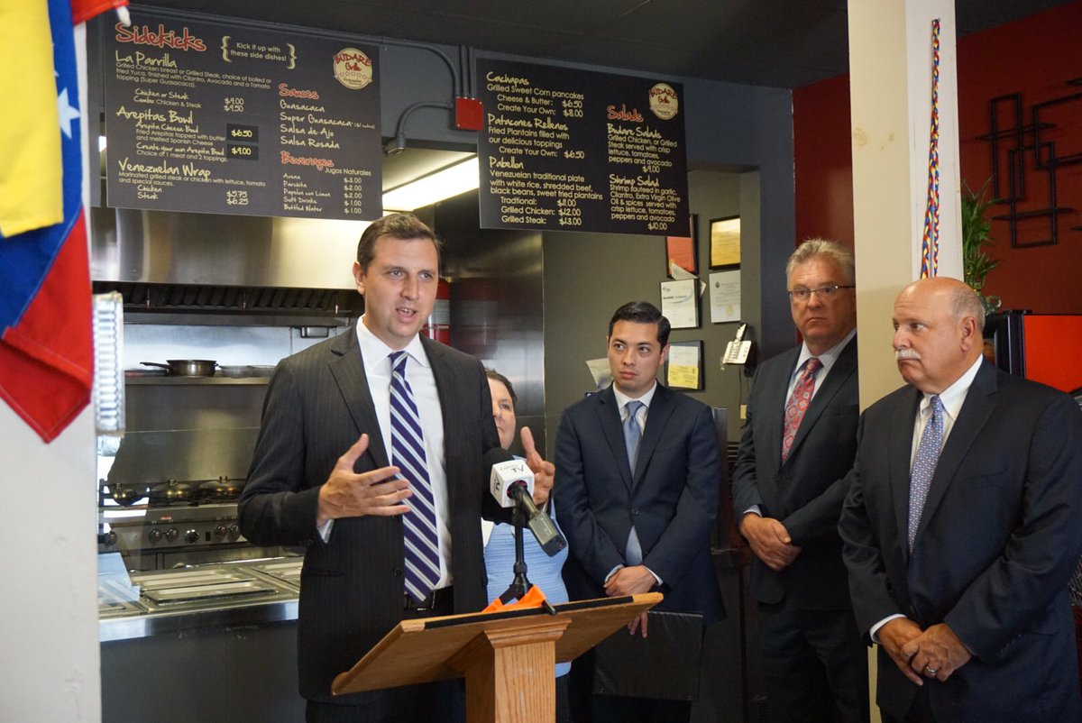 GENERAL TREASURER Seth Magaziner, left, celebrates moving $15 million in state deposits to local banks and credit unions at Budare Grille in Central Falls in August./ COURTESY R.I OFFICE OF THE GENERAL TREASURER