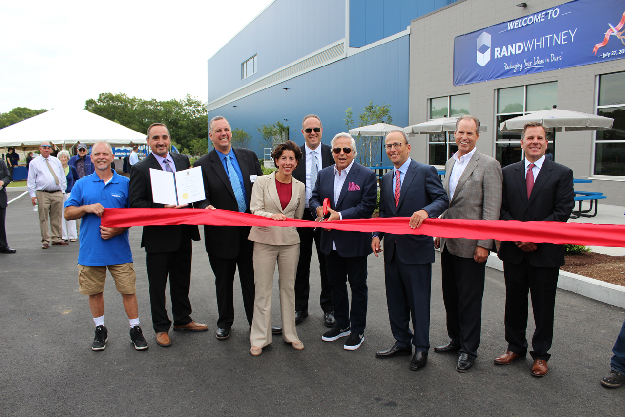 RAND-WHITNEY CONTAINER LLC held a ribbon-cutting ceremony on July 27 in celebration of the expansion of its packaging facility in Pawtucket. Rand-Whitney members were joined by state and local officials at the event. From left: Robert Gosson, 34-year employee; General Manager Adam Tominsky; Mayor Donald R. Grebien; Gov. Gina M. Raimondo; Commerce Secretary Stefan Pryor; Kraft Group owner Robert Kraft; Kraft Group President Jonathan Kraft; Procon CEO and Chairman Mark Stebbins; and CEO and President Nick Smith. /COURTESY PROCON
