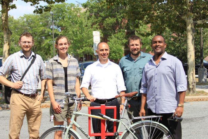 PROVIDENCE-BASED ARTS ORGANIZATION Steel Yard is donating 35 artist-designed bike racks in 16 cities and towns across the state. From left, Alex Ellis, Providence planning technician; Jenny Sparks, public projects client relations manager; Providence Mayor Jorge O. Elorza; Tim Ferland, public projects director; and Wobberson Torchon, principal of the Providence Career & Technical Academy. /COURTESY STEEL YARD