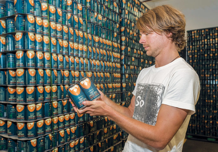 """GROWING BREW: Juan Nicolas """"Nico"""" Enriquez is co-owner of Farmer Willie's Inc., which recently became a partner at Isle Brewers Guild in Pawtucket. Their craft ginger beer is an alcoholic beverage with less sugar than competitors. / PBN PHOTO/MICHAEL SALERNO"""