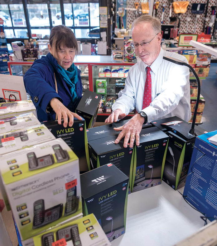 CLOSING OUT: ­Arnold Bromberg, right, co-owner of Benny's, helps Karen Weihs of Tucson, Ariz., find an LED USB desk lamp. Benny's recently announced it is closing all 31 stores in southern New England. / PBN FILE PHOTO/ ­MICHAEL SALERNO