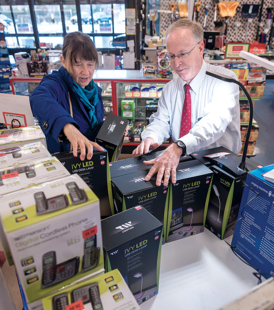 CLOSING OUT: Arnold Bromberg, right, co-owner of Benny's, helps Karen Weihs of Tucson, Ariz., find an LED USB desk lamp. Benny's recently announced it is closing all 31 stores in southern New England. / PBN FILE PHOTO/ MICHAEL SALERNO