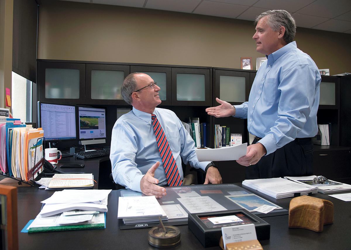 STAYING AFLOAT: Mark A. Male, left, executive vice president of the Independent Insurance Agents of Rhode Island, speaks with Sean Donaghey, senior vice president, state account executive. Male thinks flood-insurance rates will increase due to recent hurricanes. / PBN PHOTO/­MICHAEL SALERNO