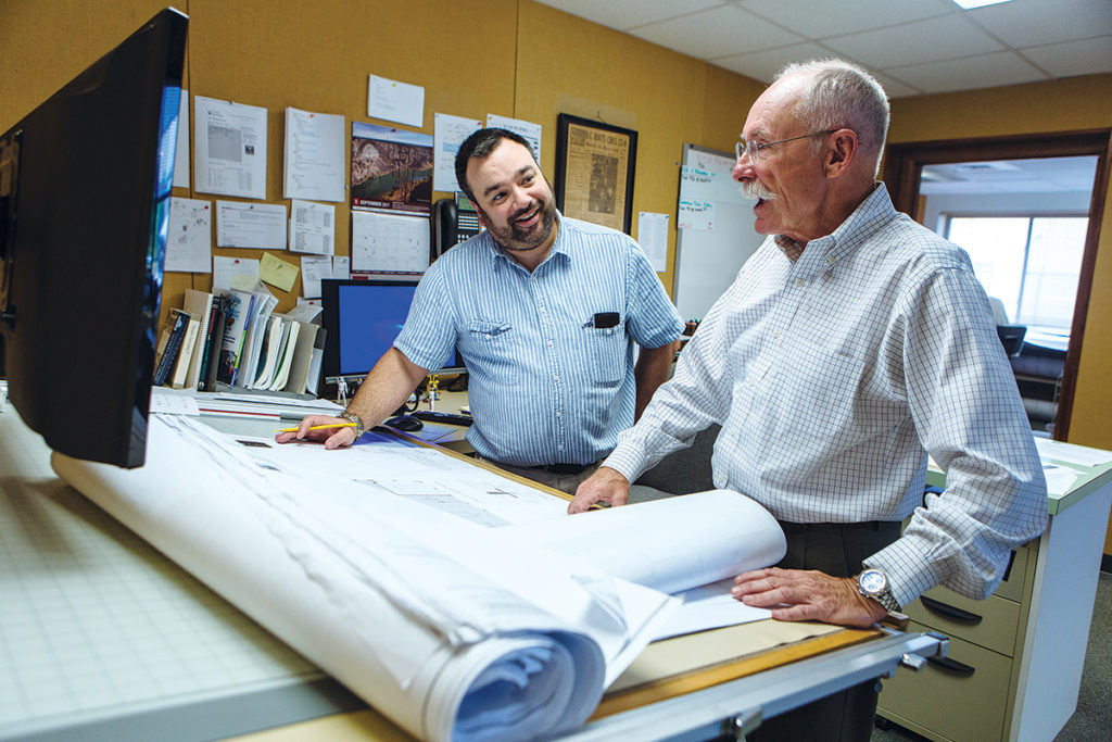IN DEMAND: Edward W. Burman Jr., right, president of general contractor E.W. Burman Inc. in Warwick, talks with estimator Bob Dandeneau. The firm was recently contracted to construct University Orthopedics in East Providence and the Welcome Center at the South Kingstown campus of the University of Rhode Island. / PBN PHOTO/RUPERT WHITELEY