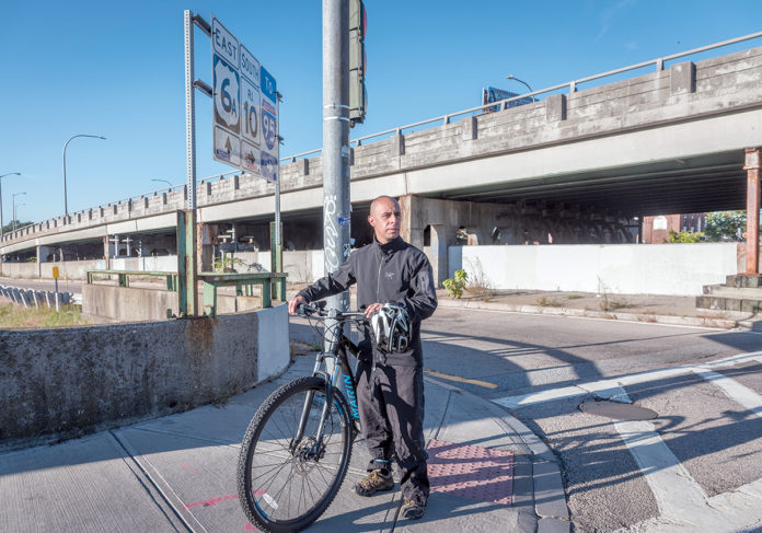 NEIGHBORHOOD ADVOCATE: Providence Mayor Jorge O. Elorza rides his bike by the 6-10 connector on Westminster Street in Providence most days. He says the roadway should connect neighborhoods, rather than divide them. / PBN FILE PHOTO/MICHAEL SALERNO