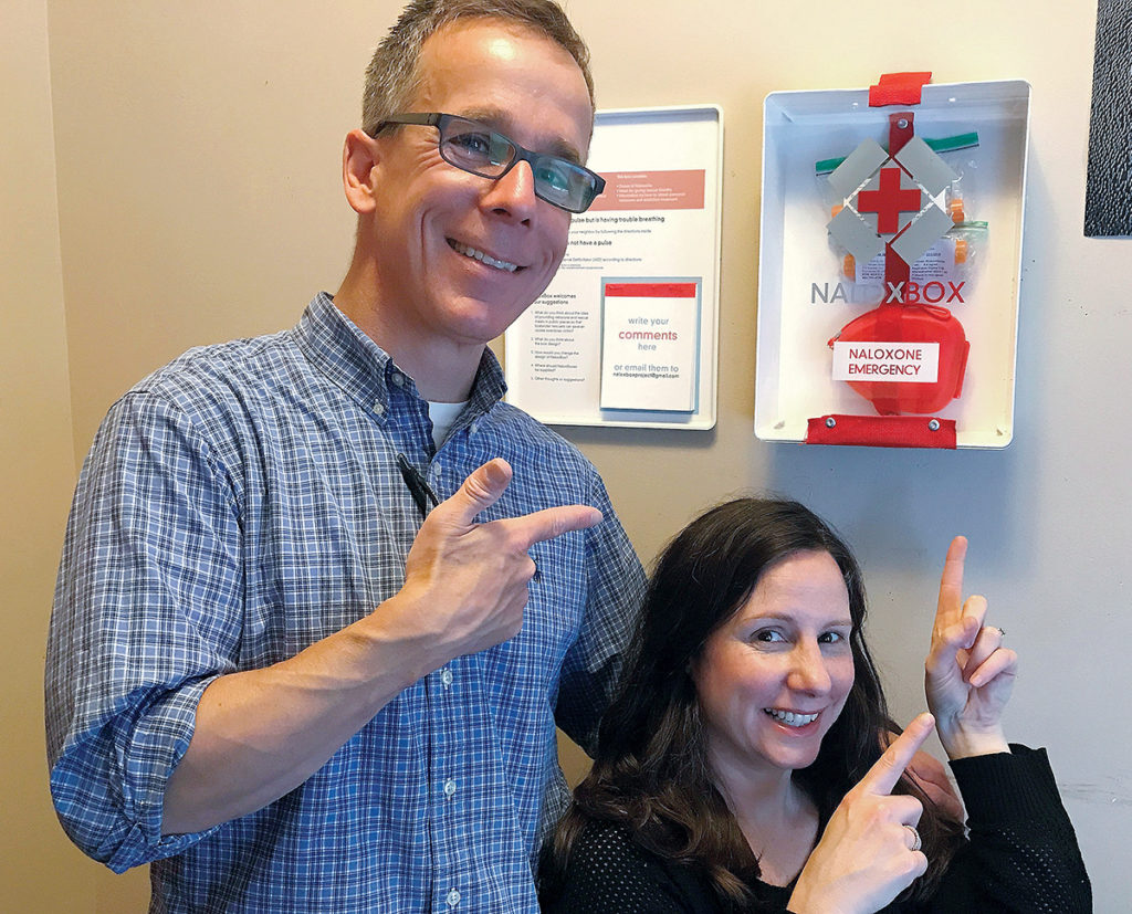 VALUABLE TOOL: NaloxBox LLC co-founders Dr. Geoff Capraro, left, and Dr. Claudia B. Rebola show off one of their NaloxBoxes, which hold tools that could potentially save the life of someone overdosing on opioids. / COURTESY NALOXBOX LLC
