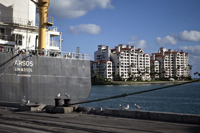 CONDOMINIUMS ON FISHER Island are seen past the Arsos container ship in the port of Miami. / BLOOMBERG FILE PHOTO/ANDREW HARRER