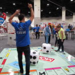 HasCon attendees and staff take turns throwing dice on a Monopoly board, one of many larger-than-life games at the event. PBN PHOTO/NICOLE DOTZENROD