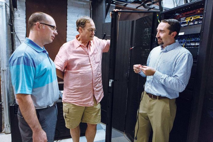 SMALL PRODUCT, big LEAP: Rich Grundy, right, president of AVTECH Software, talks about the company's new Active Power Sensor with Marketing Manager Russel Benoit, left, and company founder and CEO Michael Sigourney, middle. / PBN PHOTO/RUPERT WHITELEY