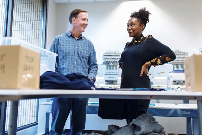 """SEWING UP GROWTH: ParsonsKellogg President Thomas Parsons """"Tom"""" Kellogg III, left, said he's just a """"T-shirt salesman."""" Embroidery specialist Monet Sanders works with T-shirts and more for the promotional-products distributor. / PBN PHOTO/RUPERT WHITELEY"""