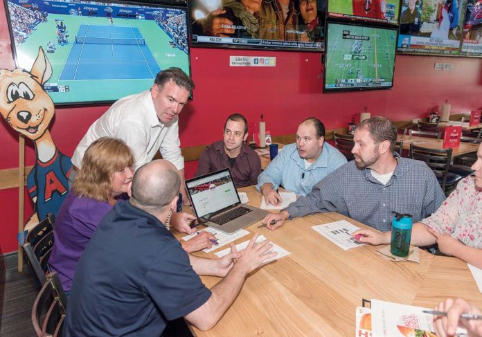 PLAY BALL! Ilya Reikhrud of Gulpfish, standing, conducts a management- training session with employees of Arooga's Grill House & Sports Bar in Warwick. / PBN PHOTO/MICHAEL SALERNO