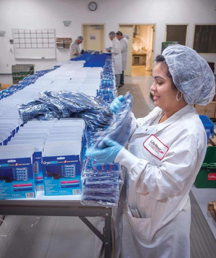WHAT A RELIEF: Life Wear Technologies staffer Rafaela Hernandez packs CryoMax products at the company's North Kingstown facility. The company is expanding its distribution to Japan and Mexico. / PBN PHOTO/MICHAEL SALERNO
