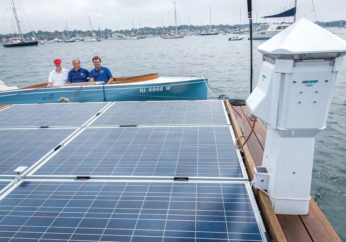CHARGED UP: PowerDocks has placed a 20-by-20-foot charging platform in Newport harbor. Using it with an eCraft boat are, from left, Rufus Van Gruisen, president of Cay Electronics Inc. and eCraft Yachts; Anthony Baro, managing partner of PowerDocks; and Chris Fagan, principal of PowerDocks. / PBN PHOTO/MICHAEL SALERNO