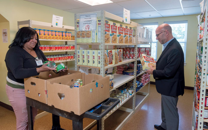 THE RHODE ISLAND Community Food Bank, a member of the nationwide network of food banks called Feeding America, suggests monetary donations are the best way Rhode Islanders can assist those in need in Texas following Hurricane Harvey. Above, Rhode Island Community Food Bank CEO Andrew Schiff helps volunteer Yve Capella stock the shelves at The Olneyville Food Center in Providence. /PBN FILE PHOTO/MICHAEL SALERNO