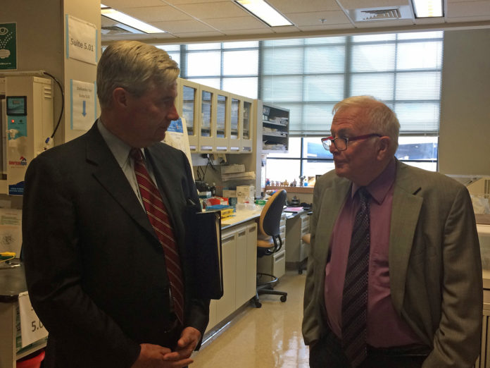 U.S. SEN. SHELDON Whitehouse, left, and Lifespan primary investigator Dr. Peter J. Quesenberry discuss his team's research at Lifespan's research lab at 1 Hoppin St. in Providence. / PBN PHOTO/ROB BORKOWSKI