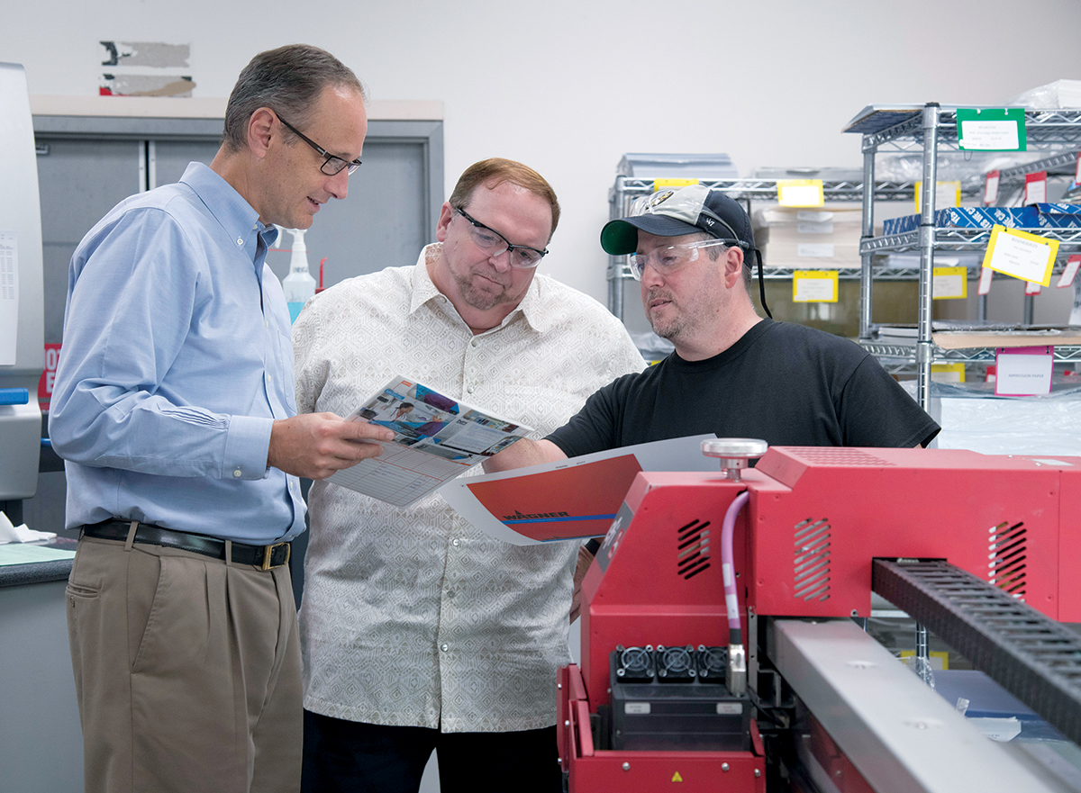 NICHE BUSINESS: From left, Renaud Megard, president of Nameplates for Industry Corp. in New Bedford, talks with Steve Moniz, pre-press and art director, and Ray Dextraze, print supervisor. The company prints on plastic and metals. / PBN PHOTO/MICHAEL SALERNO