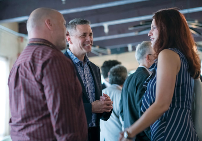 HOLISTIC APPROACH: Tim Hebert, center, Trilix CEO and founder, speaks with Dana Paul, tech sherpa at The Zen Group, left, and Sara Wilkinson, senior counsel at Duffy & Sweeney, during a launch party for Warwick-based Trilix. / PBN PHOTO/MICHAEL SALERNO